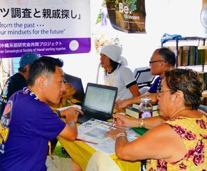 ハワイの県系人から相談を受ける県立図書館の原裕昭さん(手前左)=2日、ハワイのカピオラニ公園띱