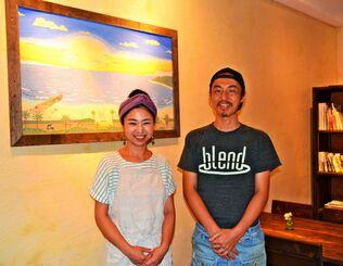 店主の高木雄二さん、仁美さん夫婦が切り盛りする「スパイスカレー PALMYRA」。琉球漆喰(しっくい)で仕上げた壁にお気に入りの砂絵が映える=沖縄市中央