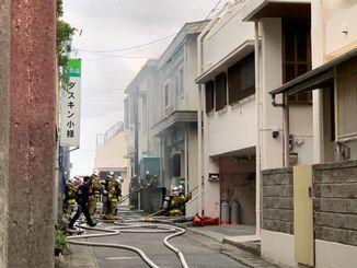 煙が立ち込める火災現場で消火活動にあたる消防隊員ら=28日午後5時15分ごろ、那覇市小禄