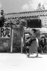 衣装箱を頭に/「ケー」と呼ばれる衣装箱を運ぶ女性。後ろには客待ちらしい人力車夫と「公設人力車駐車場」の標柱がある