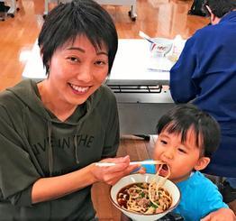 黒いスープに太麺の「唐人そば」を楽しむ参加者=15日、那覇市西・県男女共同参画センターてぃるる