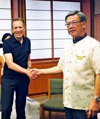 会談前に握手を交わすユー・エス・ジェイのグレン・ガンペルCEO(左)と翁長雄志知事=17日午後、県庁