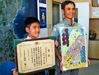 賞状と作品を手に、受賞を喜ぶ砂川耀一郎君(左)と父の徳久さん=25日、県庁