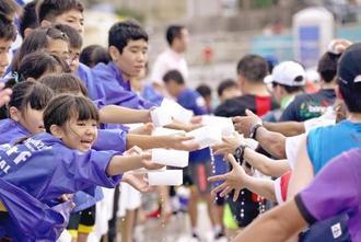 「お水です」と声を張り上げてスポンジを手渡す東風平小の児童=八重瀬町・東風平中学校前