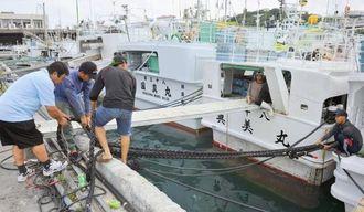 台風6号の接近に備え、漁船をロープで固定する漁師=11日午前10時半ごろ、那覇市の泊漁港