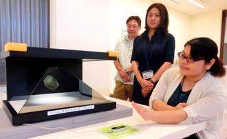 センサーに手をかざし、立体映像を自由に動かせるシステムを開発した国建システムの仲吉久美主任(右から2人目)、小橋川俊課長(同3人目)=中城村護佐丸歴史資料図書館