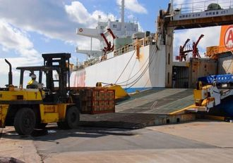定期航路開設に向けたプレ社会実験開始で、貨物が次々と船に運ばれた=10日、本部港