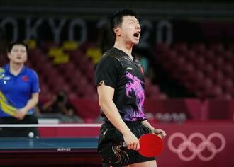 男子シングルス決勝 樊振東(奥)との中国勢対決を制し、2連覇を果たして喜ぶ馬竜=東京体育館