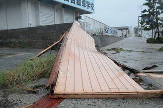 台風18号の強風で吹き飛ばされた駐車スペースを覆う壁=14日午後1時29分、宮古島市平良
