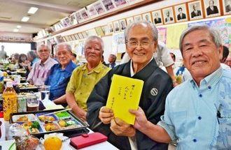 米寿を機に自分史を出版した當間幸吉さん(右から2人目)=18日、浦添市の沢岻公民館