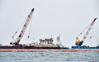 クレーンを上げ、作業を始める台船=6日午前8時59分、沖縄県名護市辺野古